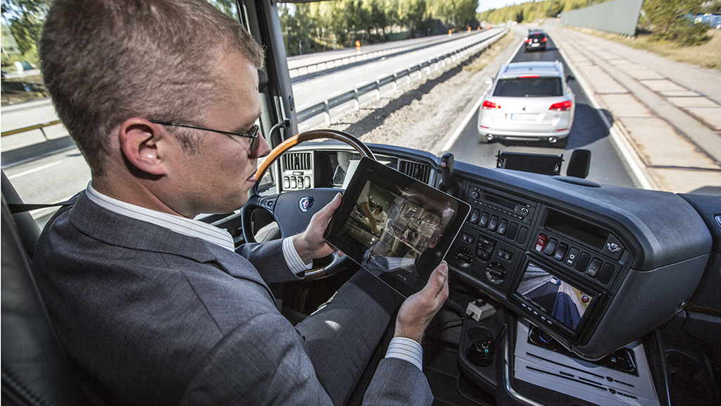 Scania senior engineer Tom Nysrom watches a film on an iPad while in the driving seat of a moving truck. Tom was demonstrating the self driving truck on the Scania test track near Stockholm in Sweden. The new truck system which, is still in development, was developed by Scania and allows the truck to drive safely, by itself, in slow moving traffic. The system is designed to enable a driver to rest while the truck is moving in heavy traffic at speeds up to 50 km per hour. Pic: Richard Pohle